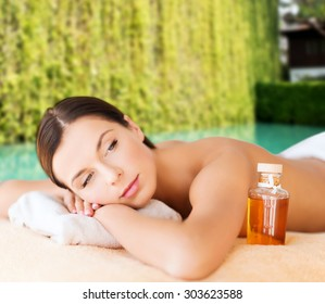 spa, beauty, people and body care concept - happy woman lying on the massage desk with oil bottle over green natural background