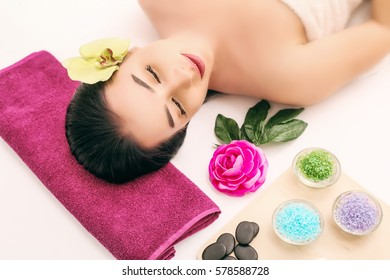 spa, beauty, people and body care concept - beautiful woman getting face treatment over holidays light background.