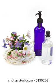 Spa beauty products - cup and saucer of spring flowers - isolated on white.