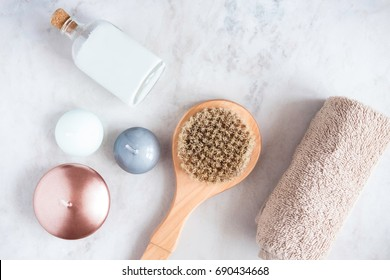 Spa beauty products on white marble table from above. Coconut oil, brush, candles, towel. Beauty blogger, massaging salon concept.