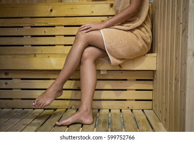 Spa beauty treatment and relaxation concept. Woman white towel relaxing in wooden sauna room.