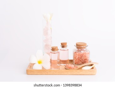 Spa and beauty treatment with rose  liquid soap,pink Himalayan salt,rose quatz stones and Plumeria  flowera on wooden tray over white  background