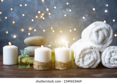 Spa, beauty treatment and wellness background Towel Cosmetic Massage oil, flowers, lights and candel