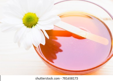Spa and body care background. Mask and body massage- a bowl of natural fragrant honey and a camomile flower, close up.