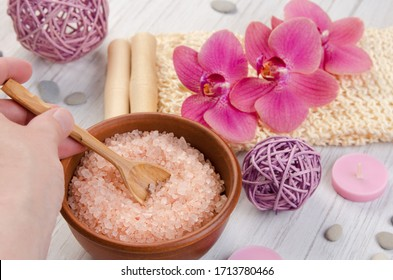 SPA body care concept. Bath salt, washcloth, candle and pink Orchid flower on white wooden background