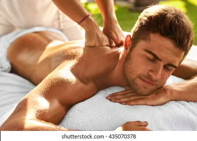 Spa Body Massage. Close Up Beautiful Sexy Healthy Happy Man Enjoying Relaxing Back Massage In Outdoor Day Beauty Salon. Masseur Hand Massaging Male With Aromatherapy Oil. Skin Care Treatment Concept