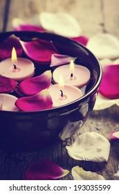 Spa candles and rose petals. retro filter.