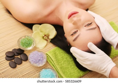 Spa. Care Facial. Beauty young woman gets a head massage in the salon.