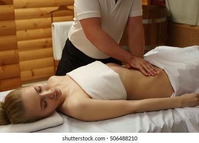 In spa center. Masseur massaging girl's belly