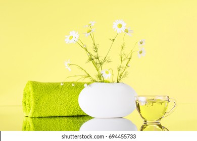 Spa. Chamomile in a vase, green towel, chamomile tea. On a yellow background