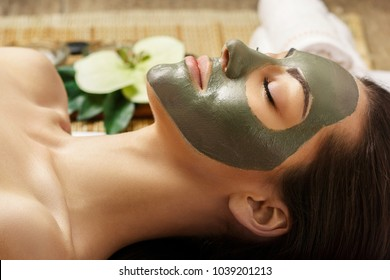 Spa Clay Mask. Woman with clay facial mask   in beauty spa. Skincare. Beauty Concept. Close-up portrait of beautiful girl with facial mask.Facial treatment. Cosmetology. Body care girl's