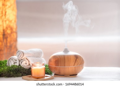 Spa composition with the aroma of a modern oil diffuser with body care products . Twisted white towels, spring greens and flowers. Spa concept for body and health care . - Shutterstock ID 1694486014