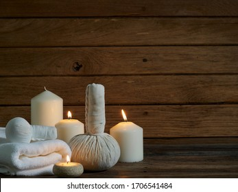 Spa composition with burning scented candles and herbal compress ball on wooden table in the dark.