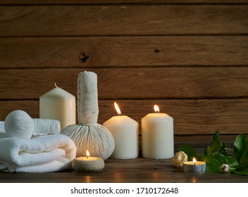 Spa composition with burning scented candles, with jasmine and herbal compress ball on wooden table in the dark.