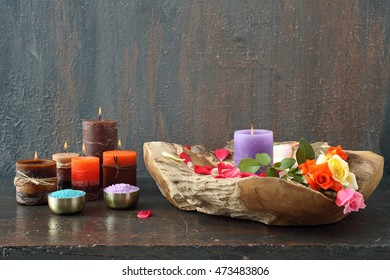 Spa composition with candles, pebbles and flowers on grey background