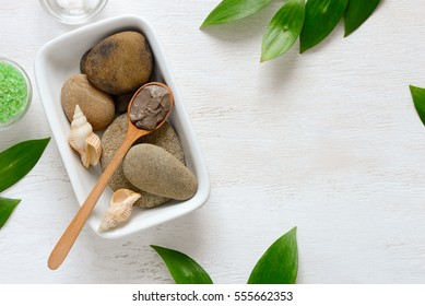 Spa composition with Dead sea mud or cosmetic clay in a spoon, view from above, space for a text