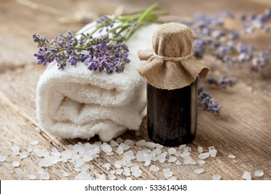 Spa composition: essential oil, lavender, towel on the old wooden background