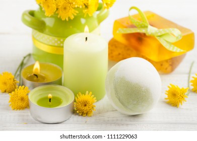 SPA composition with green bath bomb, salt, lit candles. Wooden background
