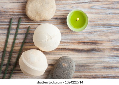 SPA composition with green tea aroma sticks, pebbles, bath bombs. Wooden background