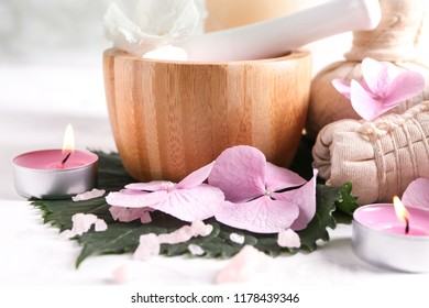 Spa composition with hydrangea flowers and burning candles on light table
