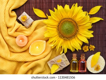 Spa composition with natural soap, candles, aroma oils in bottles and sunflower on bamboo mat. Top view