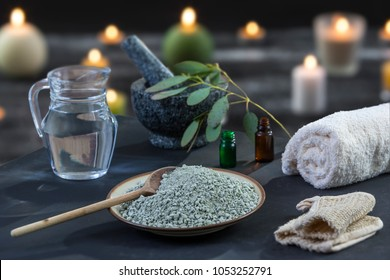 Spa composition on black wooden background. white rolled towels, candles, green herbs, eucalyptus clay mask for face and body,