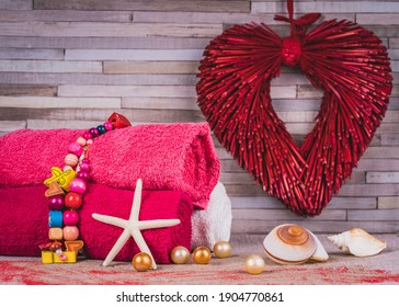 Spa composition in red-pink vibrant collors on the occasion of Valentine's Day: set of towels, heart, love, beach, shell.