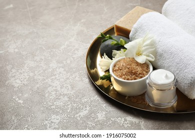 Spa composition with sea salt on grey marble table, space for text
