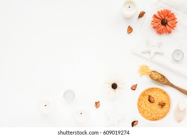 Spa composition. Sea salt, orange flowers, spa candles, bath towel on white background. Flat lay, top view