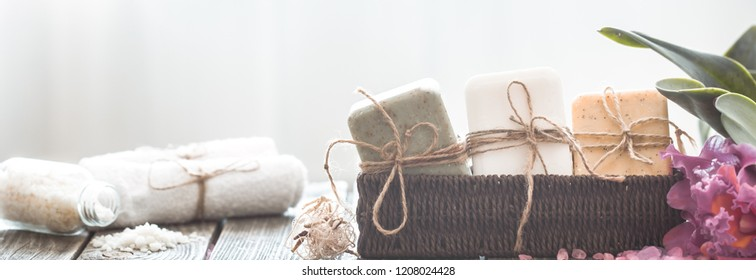 Spa composition of soap in a wicker stand with a tropical orchid on a light background, body care concept