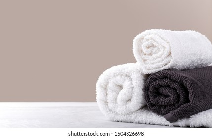 Spa composition with white and grey soft rolled cotton towels, copy space