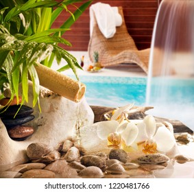 Spa concept background with stones orchids waterfall in pool and sunbed