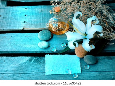 Spa concept background with white lily flower, aroma oils, water