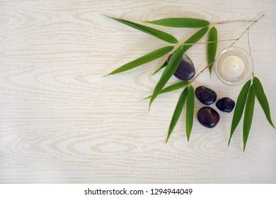 Spa concept with bamboo leaves, candle, and stones on textures background with copy space.  Shot from overhead in horizontal format.