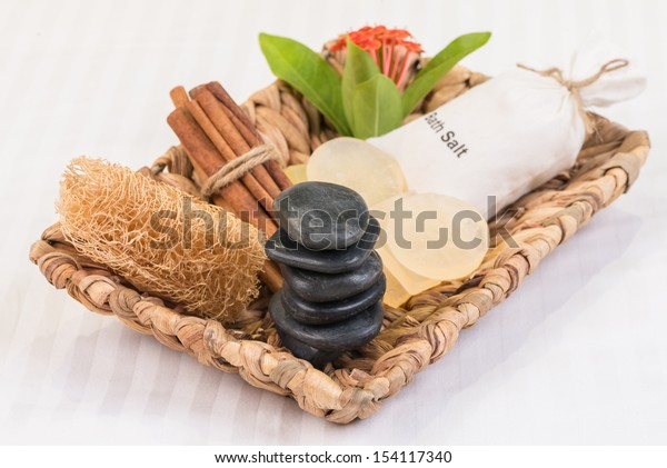Spa concept with bath salt in cotton pouch, zen stones, glycerin soaps, loofah and cinnamon sticks in banana leaf basket close up