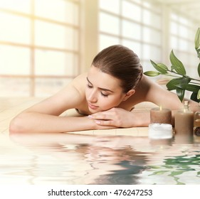 Spa concept. Beautiful woman lying on massage table near water. Blurred interior background.