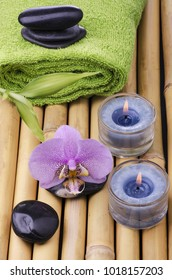 Spa concept with black massage stones, purple orchid flower and bamboo leaves and some aromatic candles
