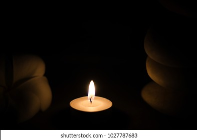 Spa concept: candle, Plumeria, stone with warm light in the dark