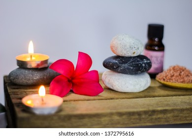 Spa concept. Close up of zen stones and frangipani flower with tea light candle in the background.