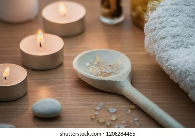 Spa concept, cosy composition with bath salt, wooden spoon, stones and candles on spa salon wooden table with healthy relax meditative atmosphere