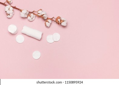 Spa concept. Flat lay background with cotton branch, cotton pads. Cotton Cosmetic Makeup Removers Tampons. Hygienic sanitary swabs on the pink background Top view with copy space