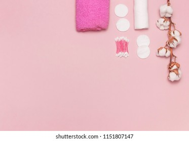 Spa concept. Flat lay background with cotton branch, cotton pads, eared sticks, pink towel. Cotton Cosmetic Makeup Removers Tampons. Hygienic sanitary swabs on the pink background Top view copy space