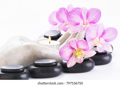 Spa concept with hot stones and candle on palm shaped candle holder