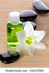 spa concept - liquid soap, stones and white flower