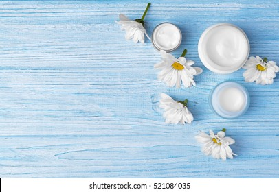Spa concept. Nourishing cream and daisy flowers on light wooden table