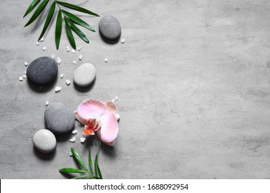 Spa concept on stone background, palm leaves, flower and zen, grey stones, top view, copy space