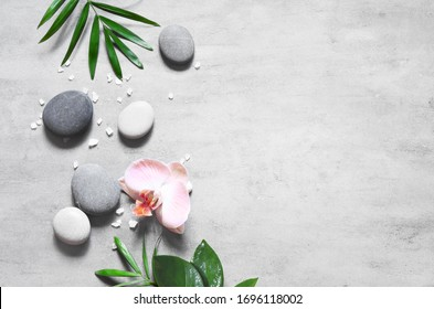 Spa concept on stone background, palm leaves, flower and zen, grey stones, salt, top view, copy space