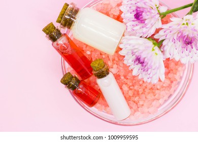 Spa concept. Spa procedures - essential oil and natural cream in glass jars, with bath seasalt and beautiful flowers. Beauty, aromatherapy concept, bodycare