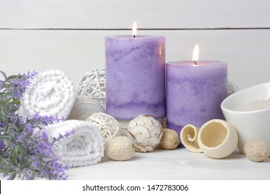 spa concept of purple burning candles decorated in natural dried potpourri, lavender, white towels, bath salts, dried floral on white wooden rustic background