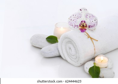 Spa concept with rolled towel, orchid, candle